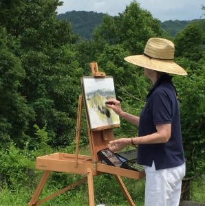 Ellen placed her easel to draw the rolling hills.