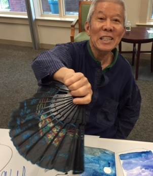 Wan Lee dries the paint with a fan.